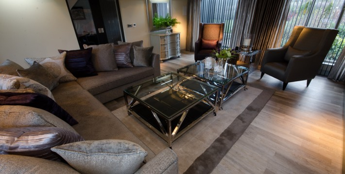 Living room contemporary Interior Design with bespoke sofa, arm chairs, table units and blinds in deep colours.